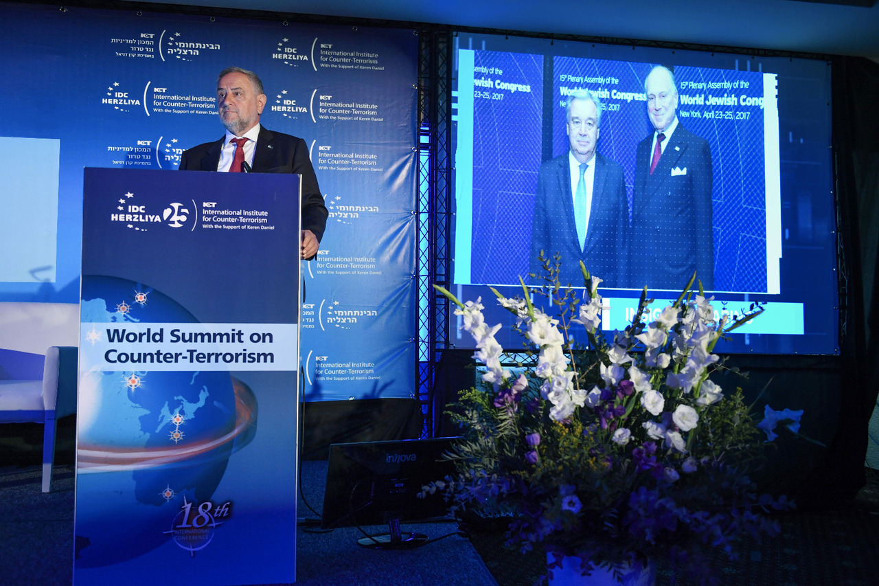 WJC CEO Robert Singer addressing conference, in front of photo of WJC President Ronald S. Lauder and UN Sec. Gen. Antonio Guterres. (c) Shahar Azran